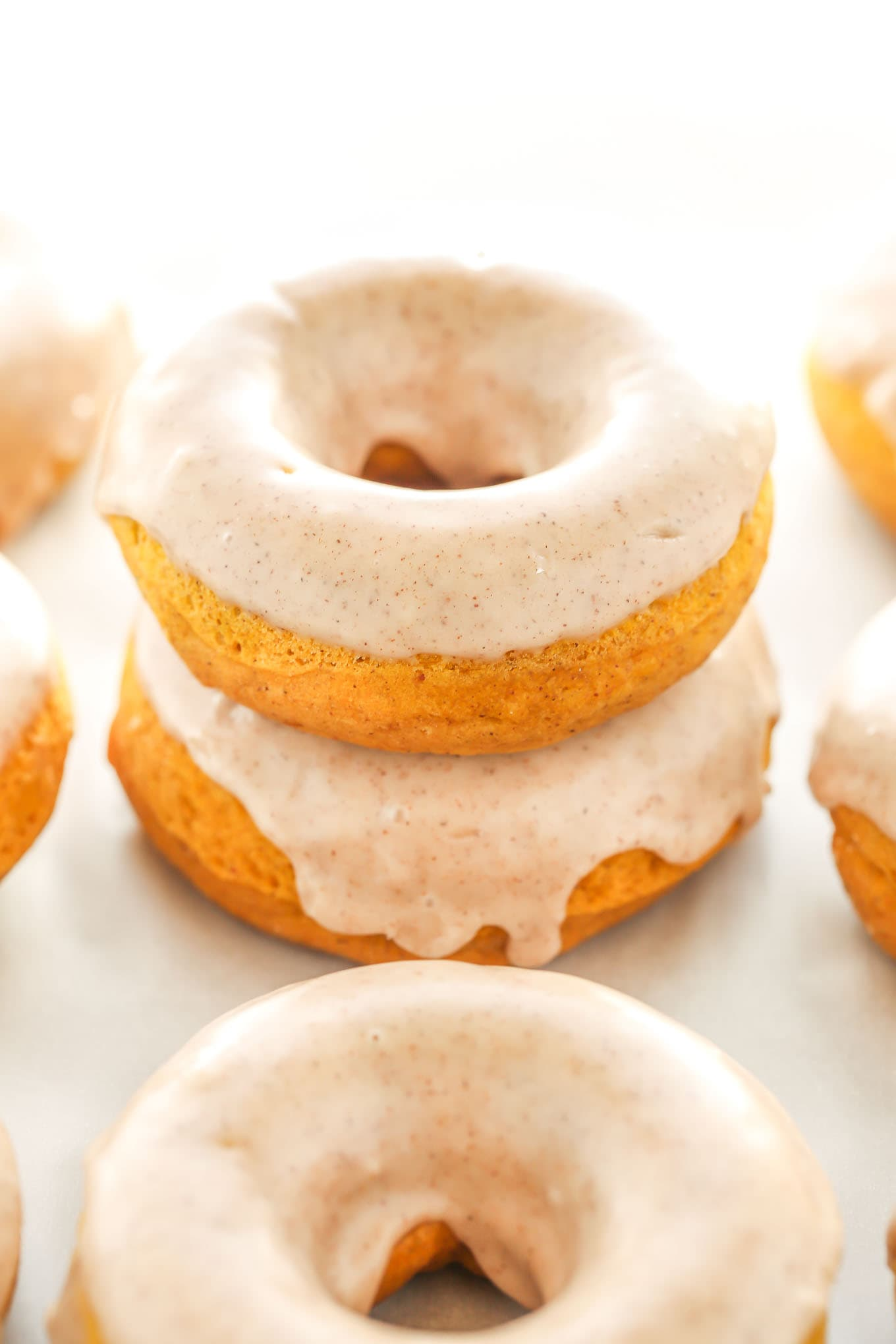 A stack of two pumpkin donuts. Additional donuts surround the stack.