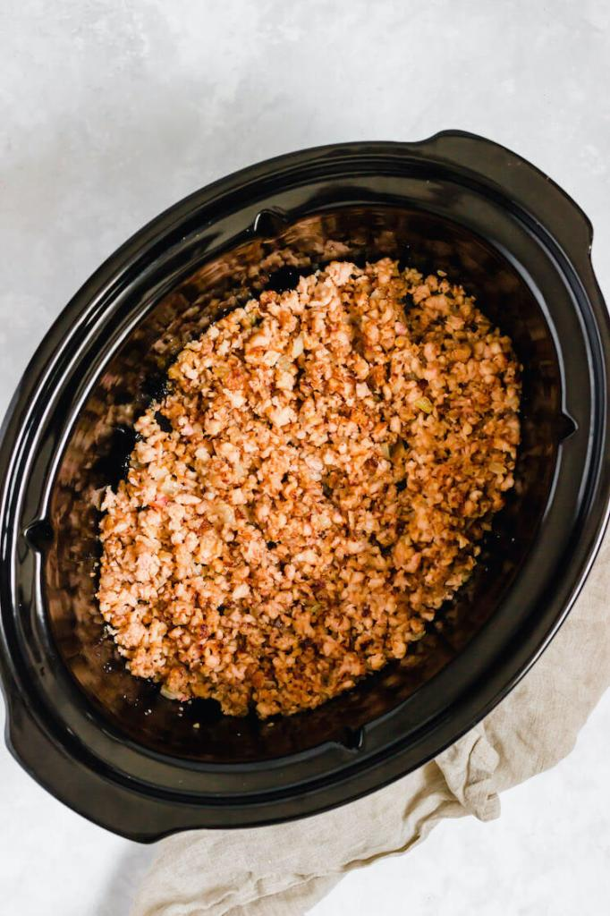 A crockpot filled with cooked ground turkey and onions.