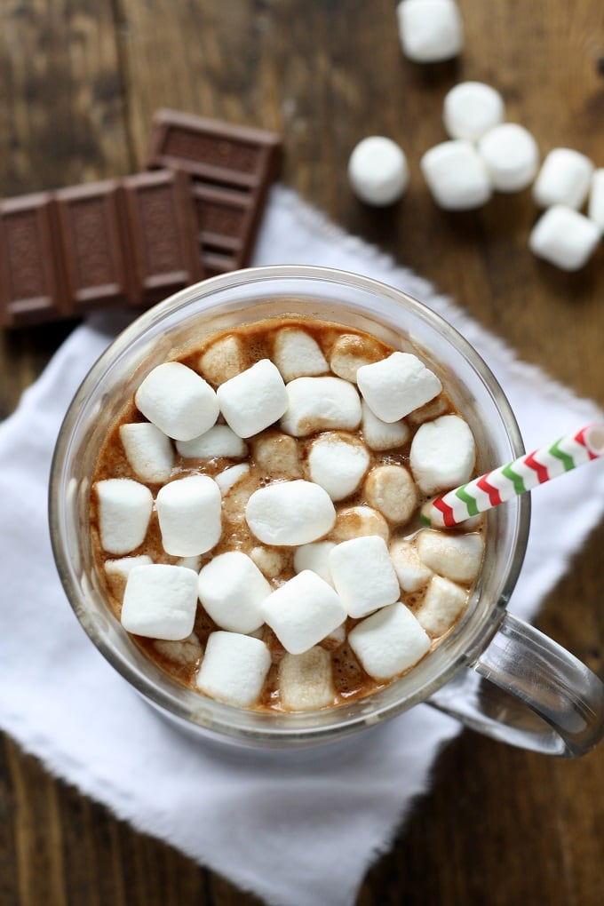 Overhead view of hot chocolate topped with marshmallows in a glass mug. Chocolate squares and mini marshmallows rest in the background.