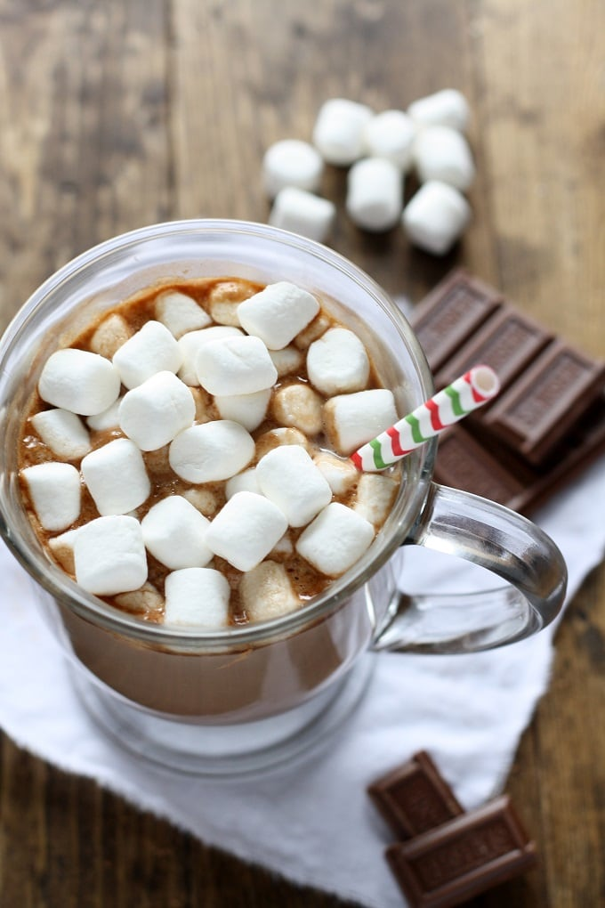 Mug of homemade hot chocolate topped with mini marshmallows and a straw. Chocolate squares and marshmallows rest in the background.