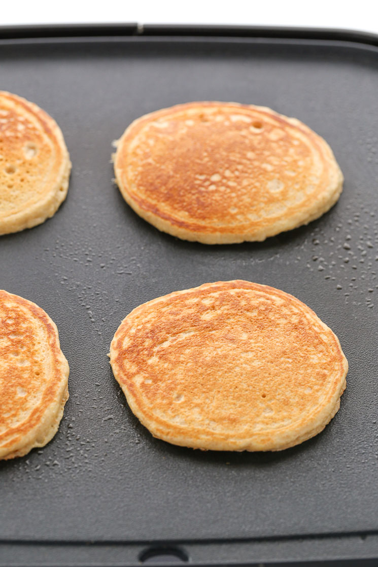A black grilled topped with fully cooked whole wheat pancakes.