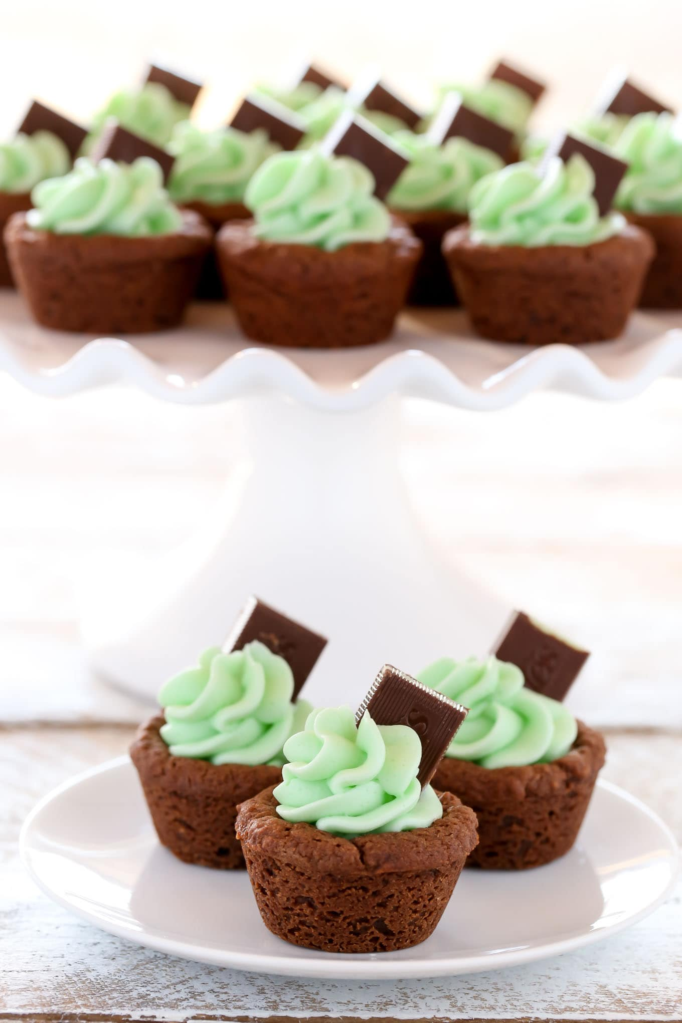 Chocolate cookie cups filled with an easy mint frosting and topped with an andes mint. These Mint Chocolate Cookie Cups are a perfect treat for St. Patrick's Day or mint chocolate lovers!