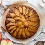 An overhead shot of caramel apple upside-down cake with apples and milk around it.
