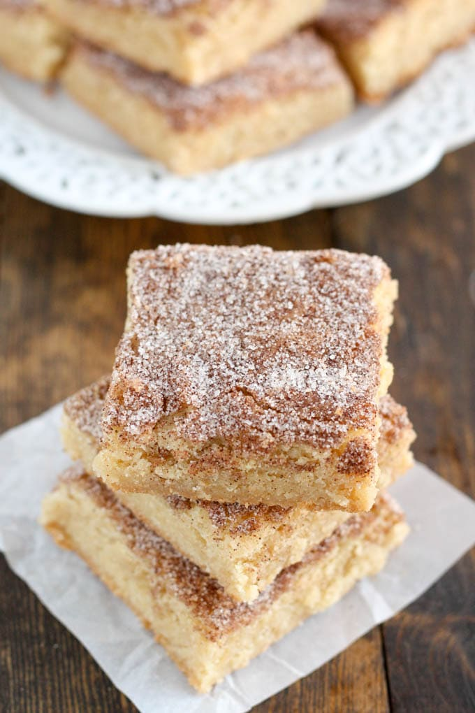 A stack of three snickerdoodle blondie bars on a square of parchment paper.