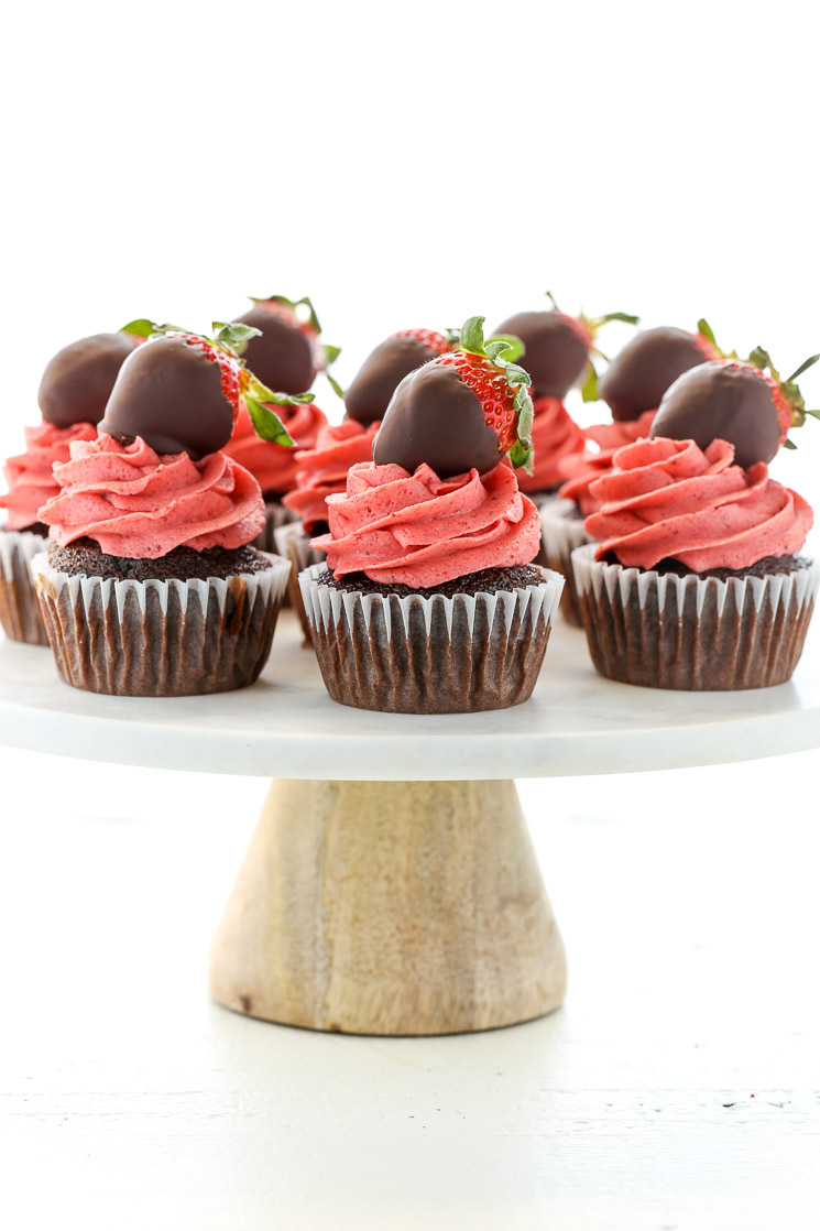 Chocolate cupcakes topped with strawberry buttercream frosting and chocolate covered strawberries on top of a white marble cake stand.