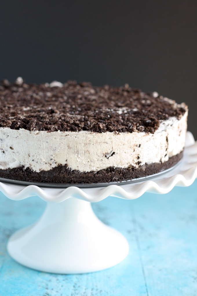 A side view of a no-bake Oreo cheesecake on a white cake stand.