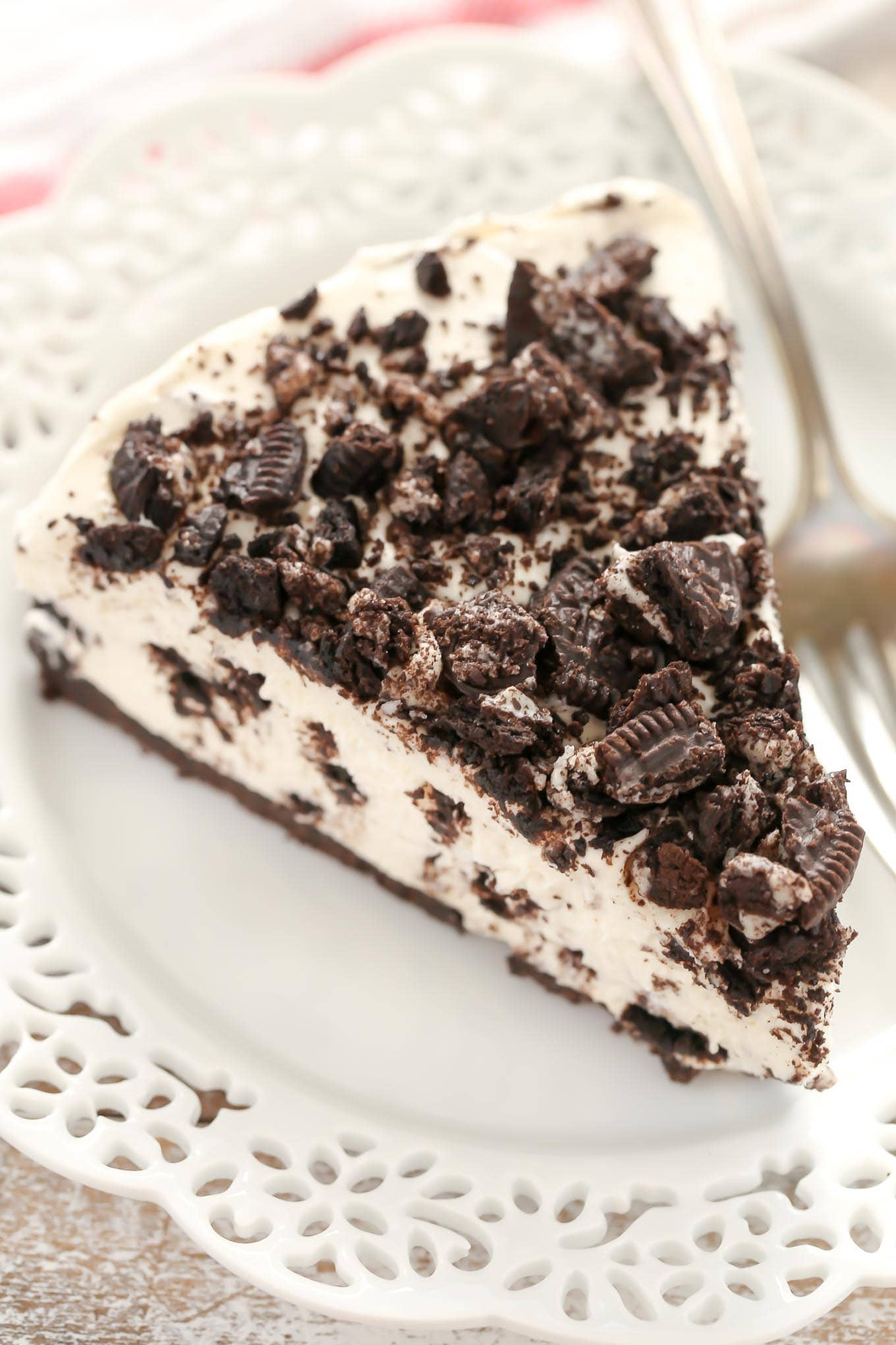 An overhead view of a slice of Oreo cheesecake on a white plate with a fork.