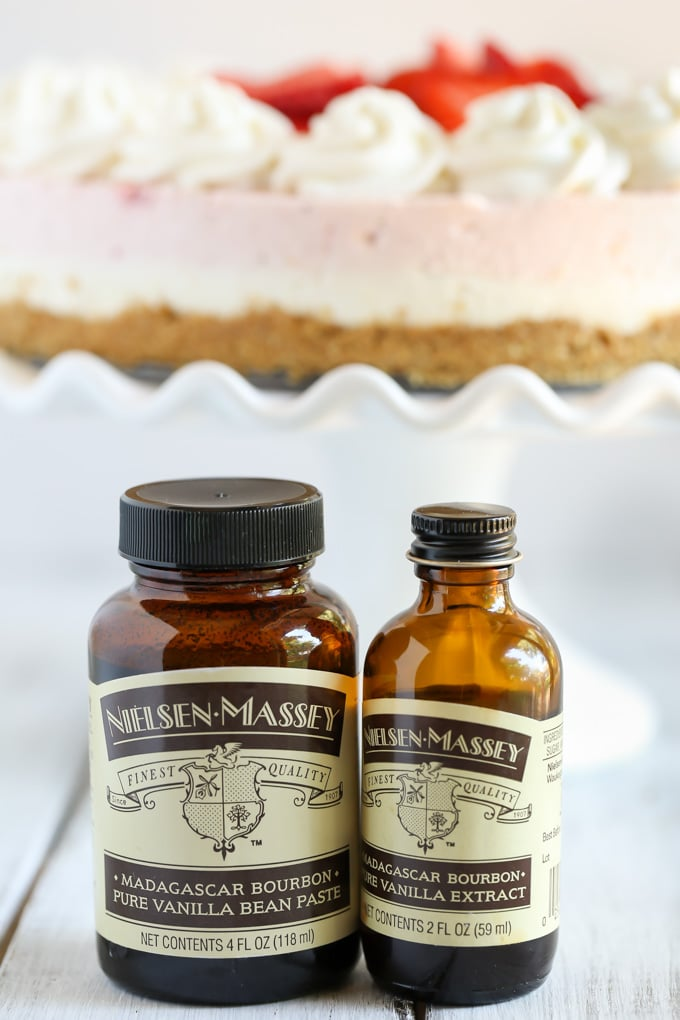 A bottle of vanilla bean paste and a bottle of vanilla extract. In the background is a fresh strawberry cheesecake on a cake stand.