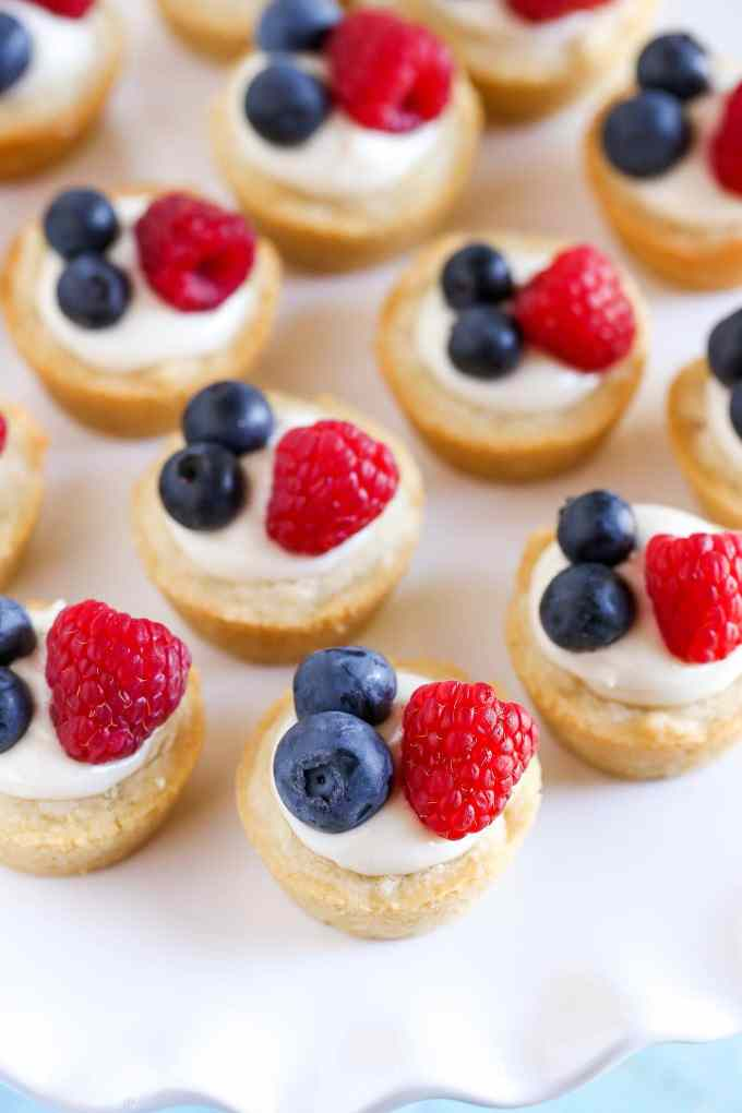 Sugar cookie cups filled with a no-bake lemon cream cheese filling and topped with fresh berries. These Lemon Berry Cheesecake Sugar Cookie Cups make the perfect summer dessert!