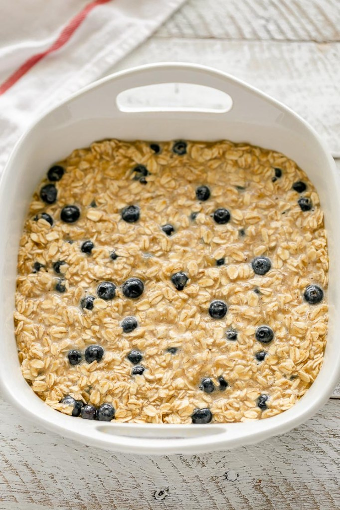 A white baking dish filled with the prepared baked oatmeal mixture.