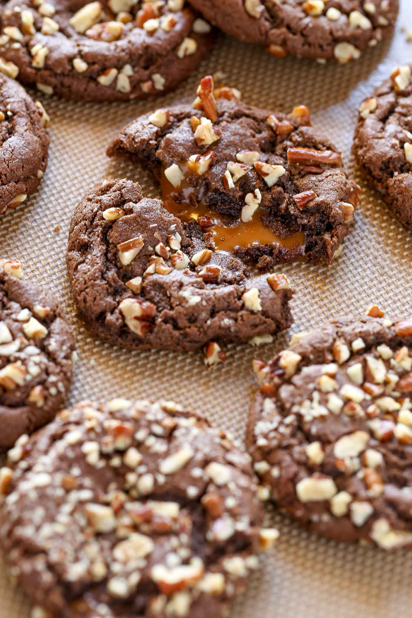 A close up view of chocolate turtle cookies on a baking sheet.