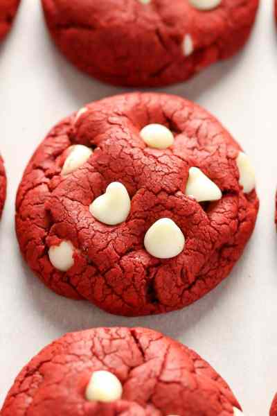 Red velvet cookies lined up on a piece of parchment paper.