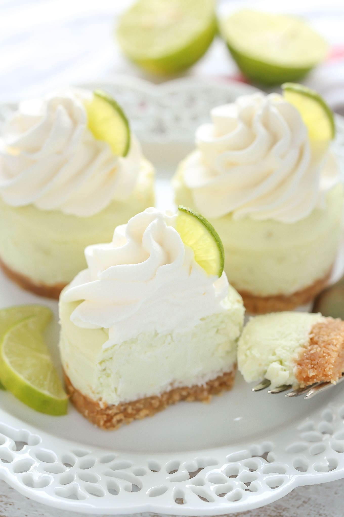 A white plate with three mini key lime cheesecakes on it. A lime wedge rests on one side and a fork rests on the other.