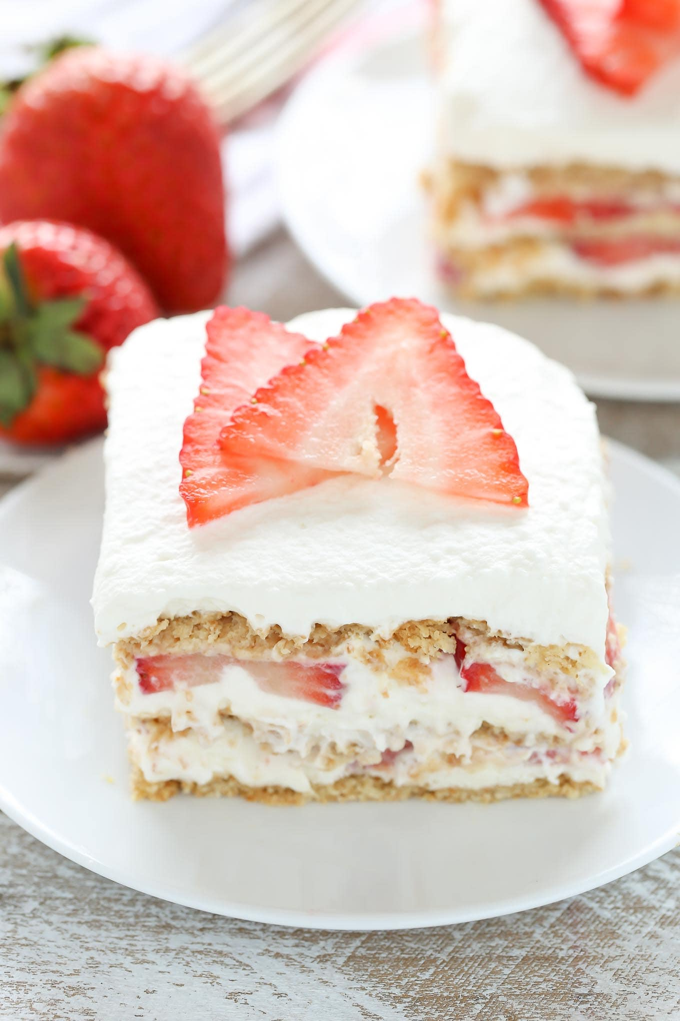 Close up of a slice of strawberry cream cheese icebox cake on a white dessert plate. Another slice and some fresh berries rest in the background.