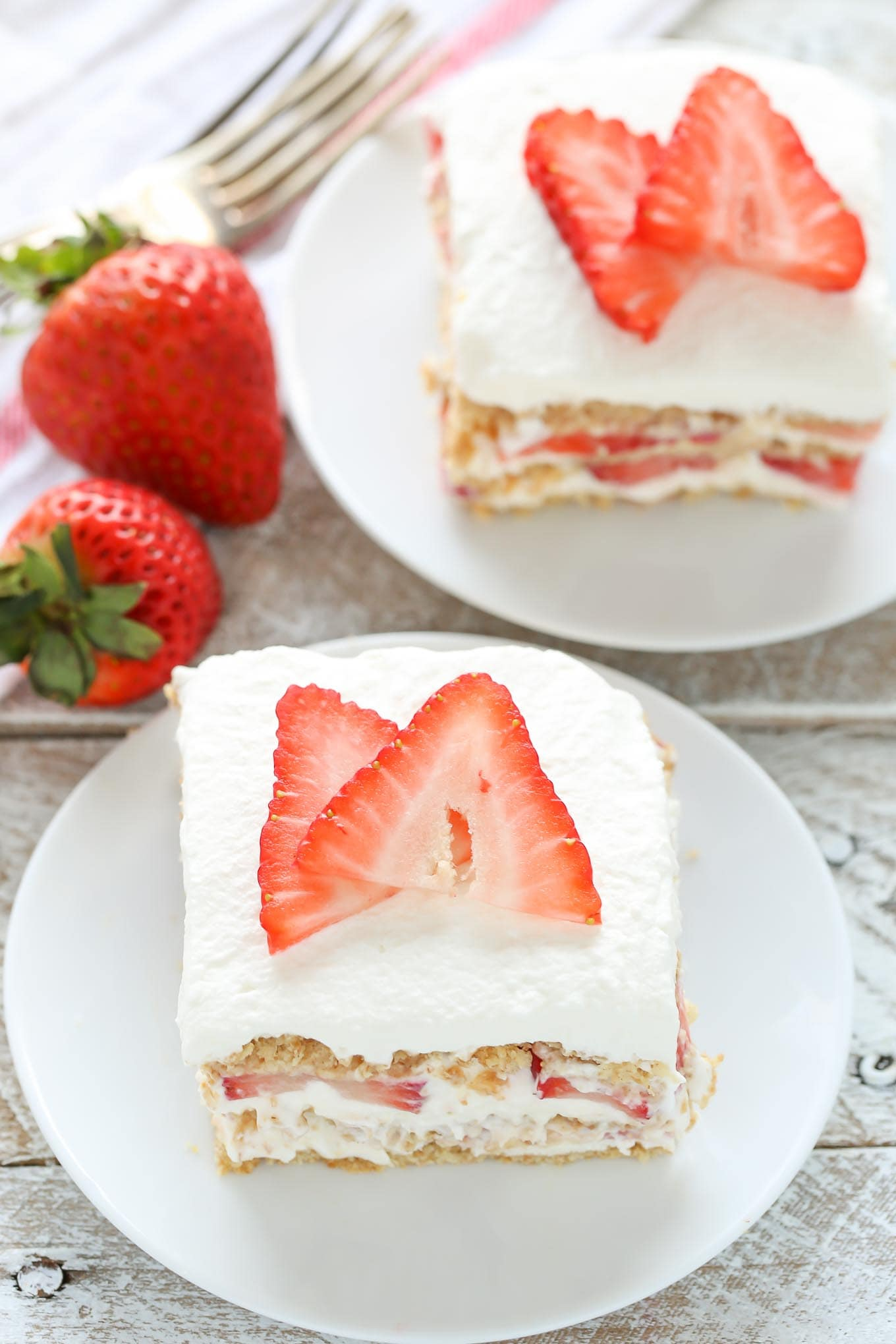 Two slices of strawberry icebox cake on white dessert plates. Two fresh berries and a fork rest on the side.