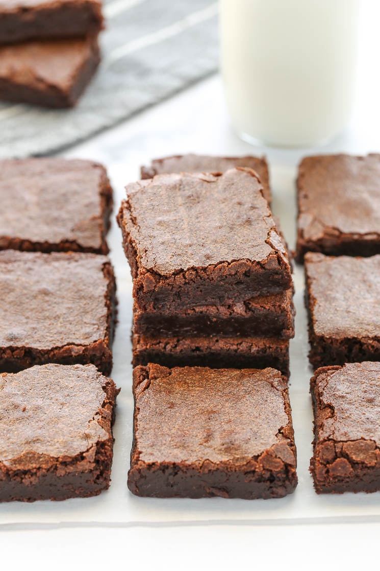 A stack of sliced brownies with other brownies around it, a glass of milk and more brownies in the background.