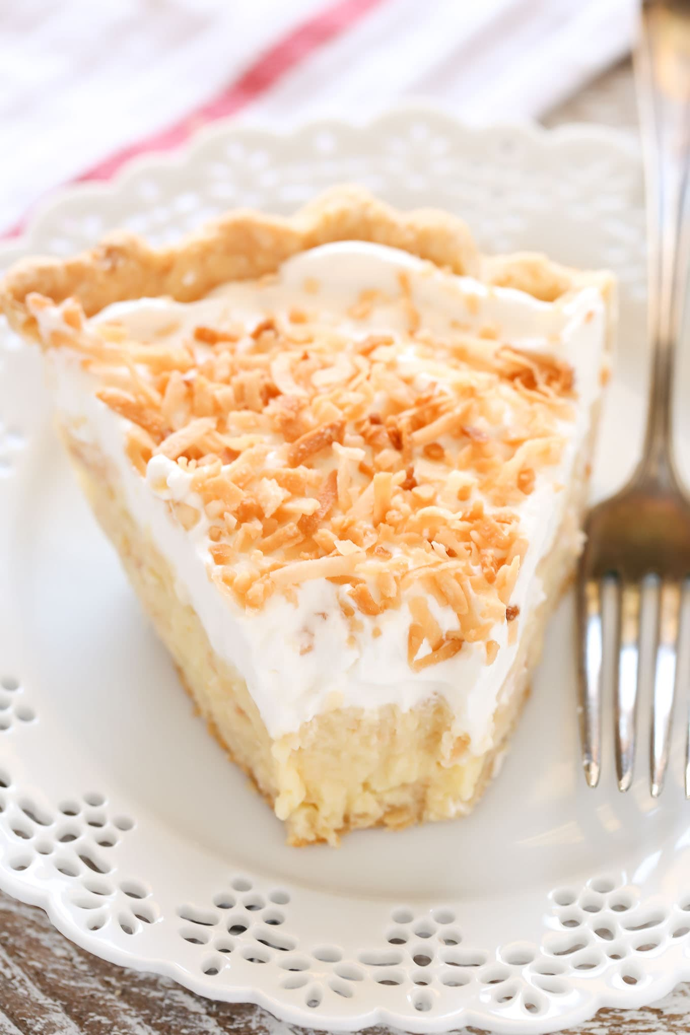 A homemade pie crust filled with a creamy coconut filling topped with whipped cream and toasted coconut. This homemade coconut cream pie recipe is so easy to make and delicious!