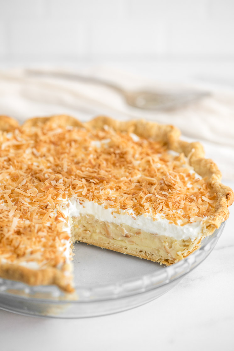 A close-up of a coconut cream pie with a slice taken out of it.