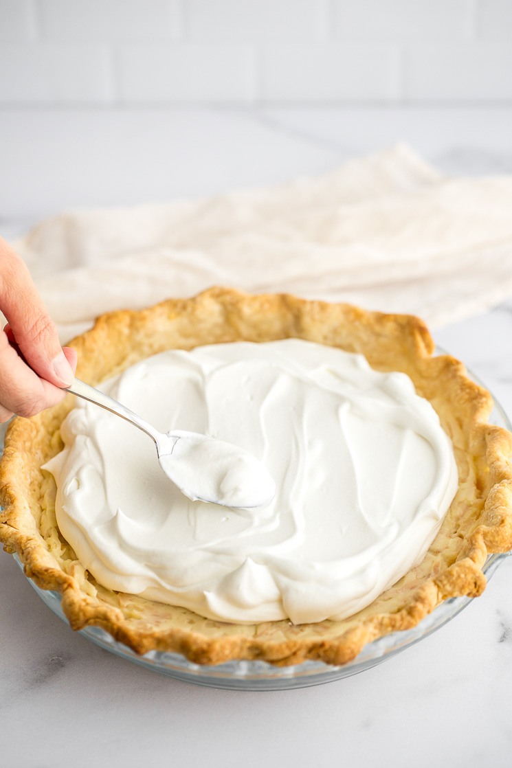 A close-up of whipped cream being added to the top of the pie.