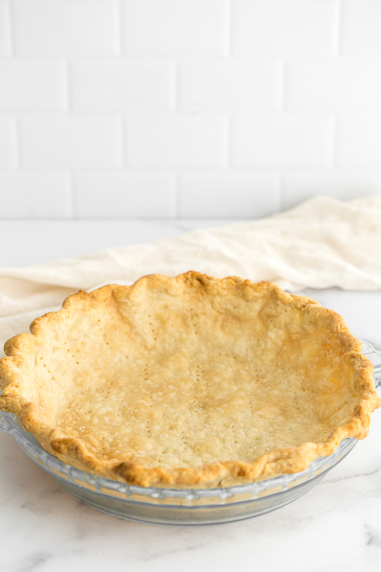 A homemade pie crust in a pie dish sitting on top of a marble surface.