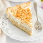 A close-up image of a slice of coconut cream pie on a plate.
