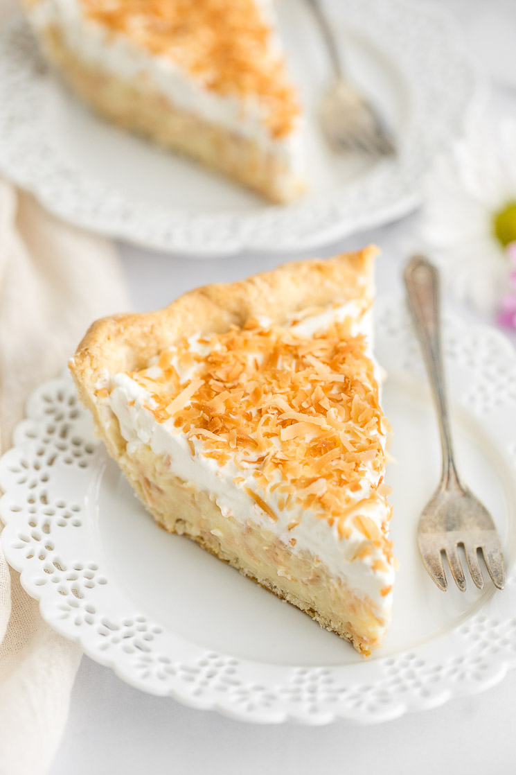 A slice of coconut cream pie on a decorative white plate with another slice in the background.