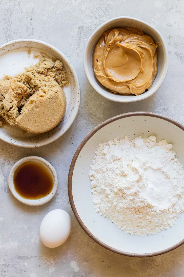 The ingredients needed to make peanut butter cookies in bowls on top of a rustic gray surface.