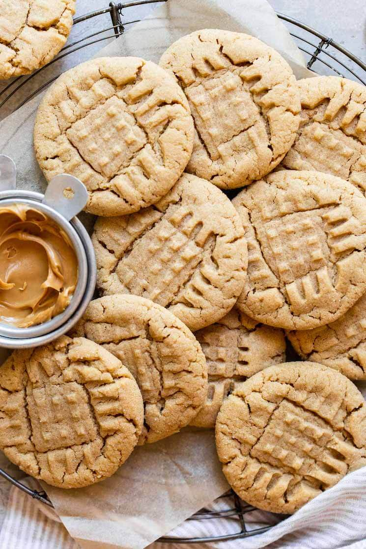 An overhead view of peanut butter cookies on a round cooling rack with a metal cup of peanut butter off to the side.