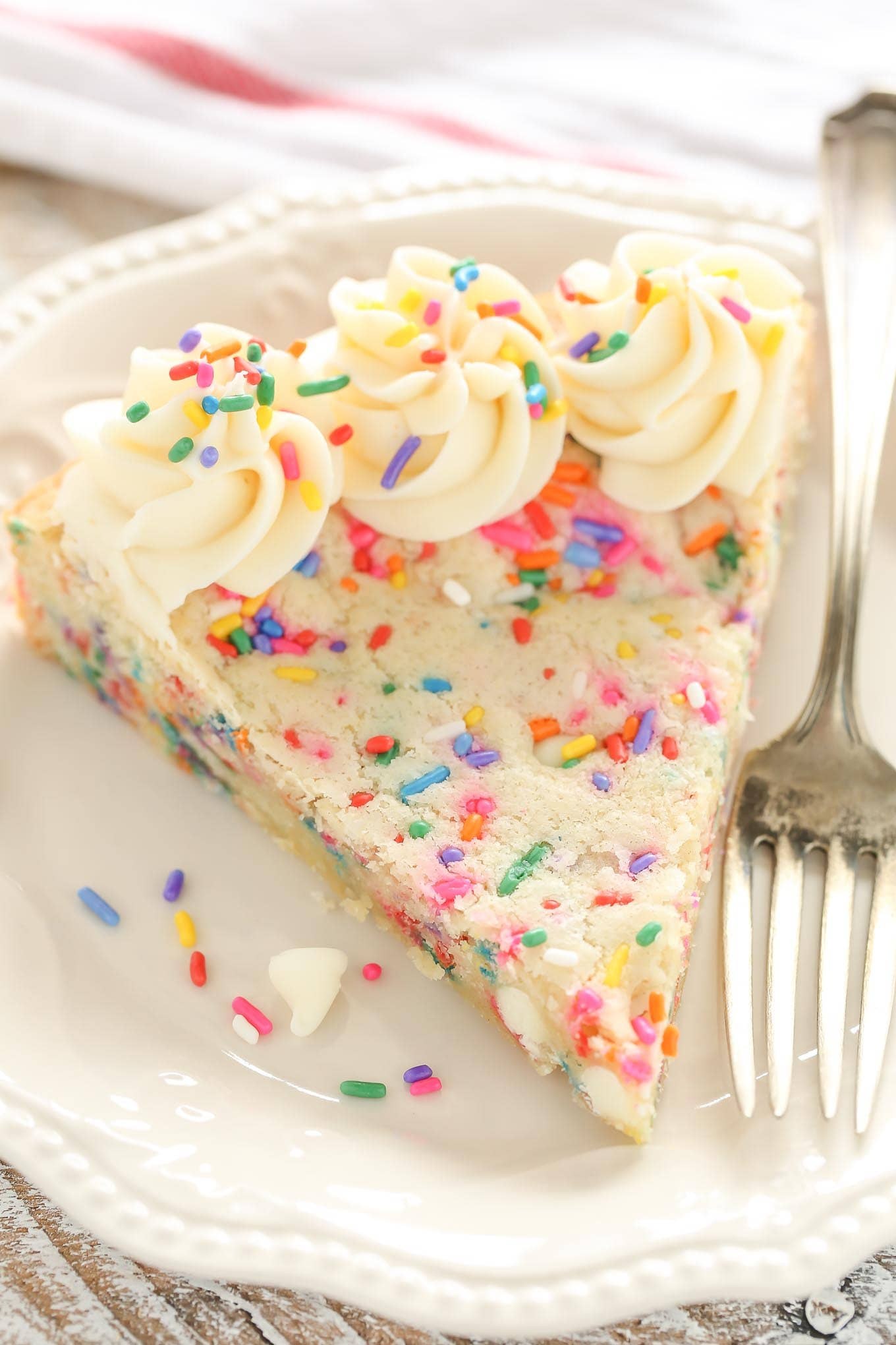 A sugar cookie cake withsprinkles, whitechocolate chips, and topped with a homemade vanilla frosting. This Funfetti Sugar Cookie Cake is easy to make and aperfect dessert for any occasion!