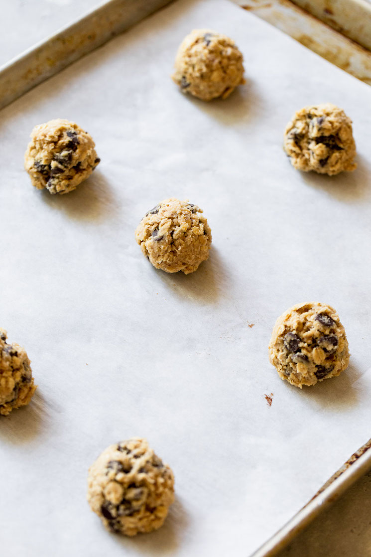 An antique baking sheet lined with parchment paper holding balls of oatmeal chocolate chip cookie dough ready to be baked.