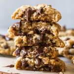 A stack of oatmeal chocolate chip cookies cut in half with melted chocolate running down the front.