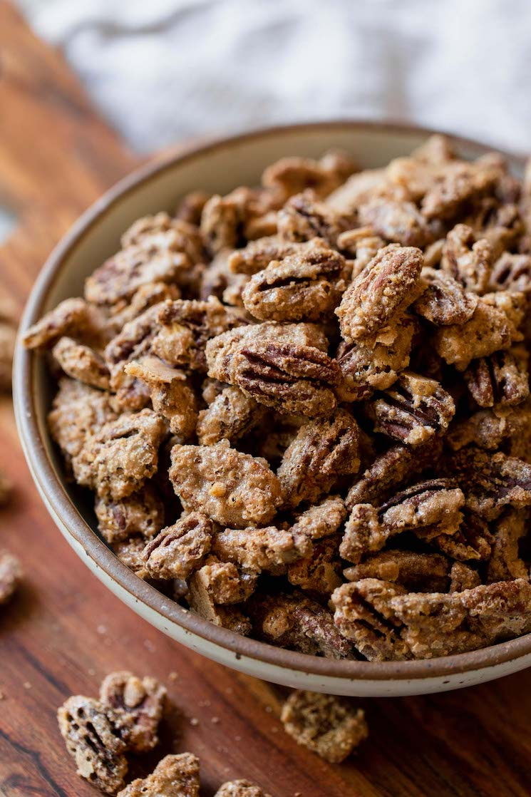 A rustic clay bowl filled with candied pecans resting on top of a wooden tray.