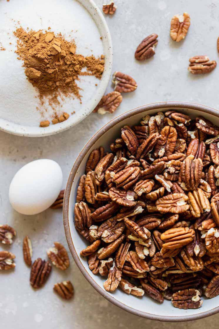 The ingredients needed for candied pecans in different bowls on a gray surface.