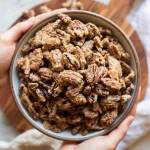 A bowl of candied pecans being held over a wooden surface.