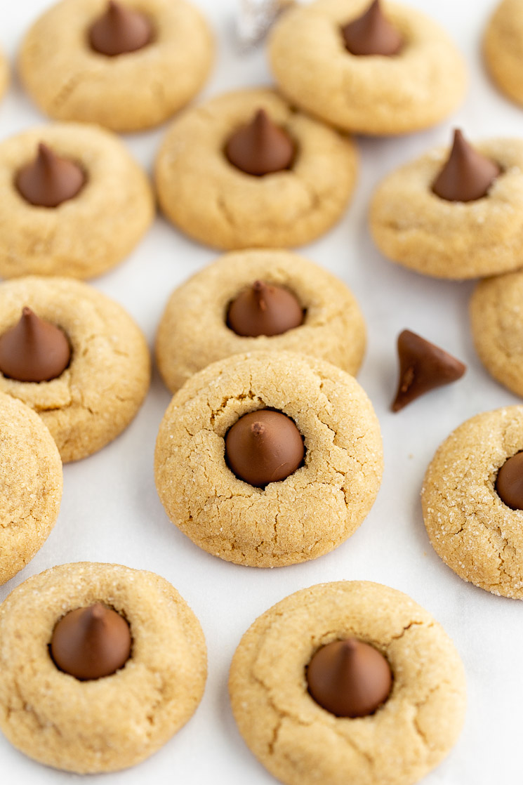 A baking sheet covered in peanut butter blossoms with chocolate kisses mixed in.