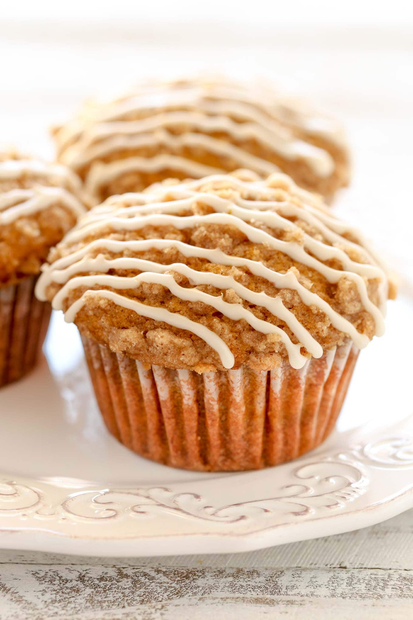 Three of the best ever pumpkin muffins topped with vanilla glaze on a white plate.