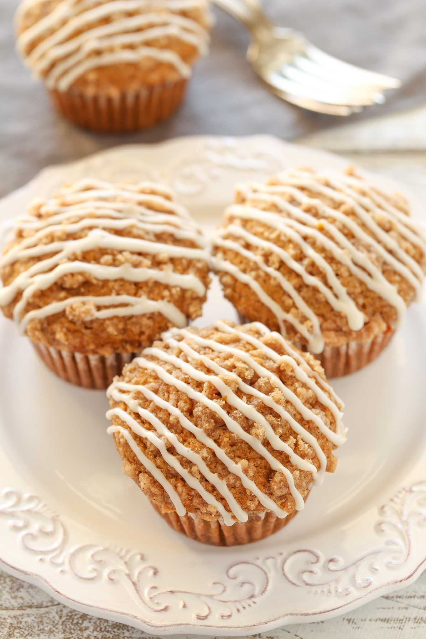 An easy recipe for soft pumpkin muffins with a crumb topping and vanilla glaze. These pumpkin crumb muffins are perfect for a fall breakfast or dessert!