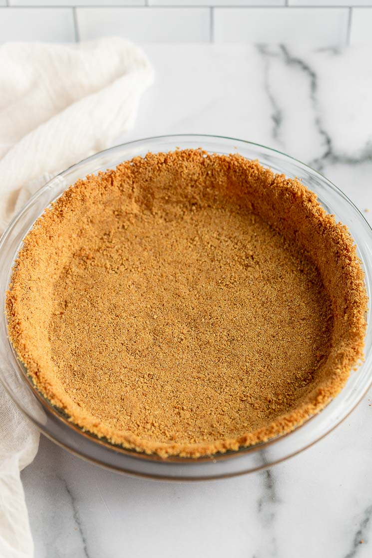 A baked graham cracker crust in a pie dish.