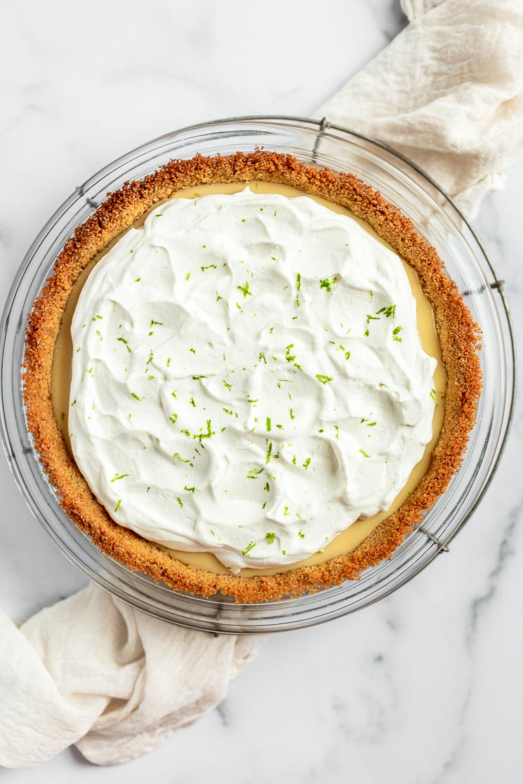 A key lime pie topped with whipped cream on an antique wire rack.