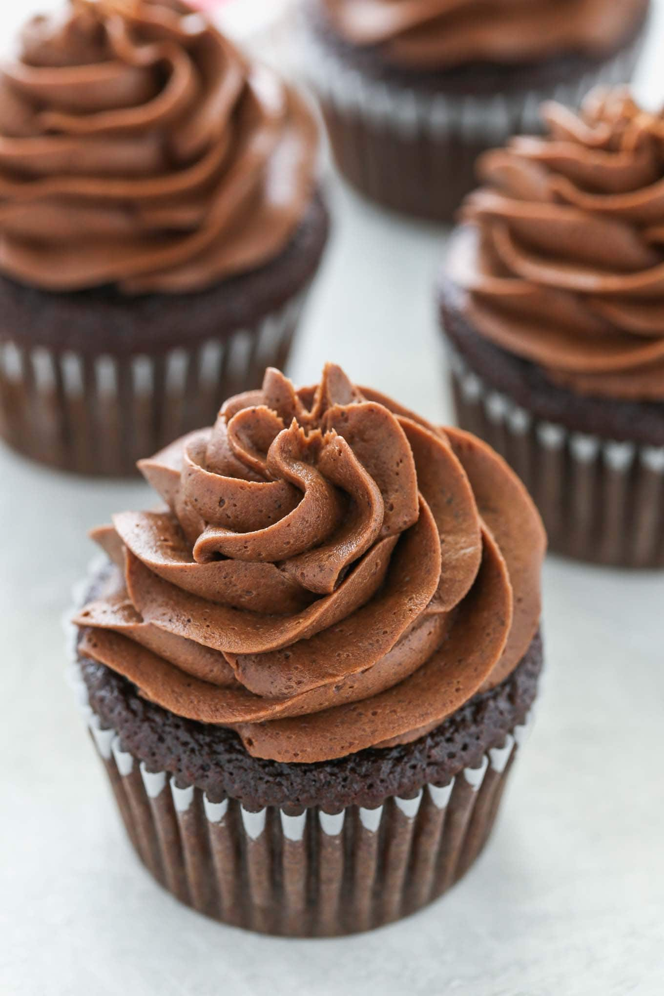 Four chocolate cupcakes topped with homemade chocolate frosting.