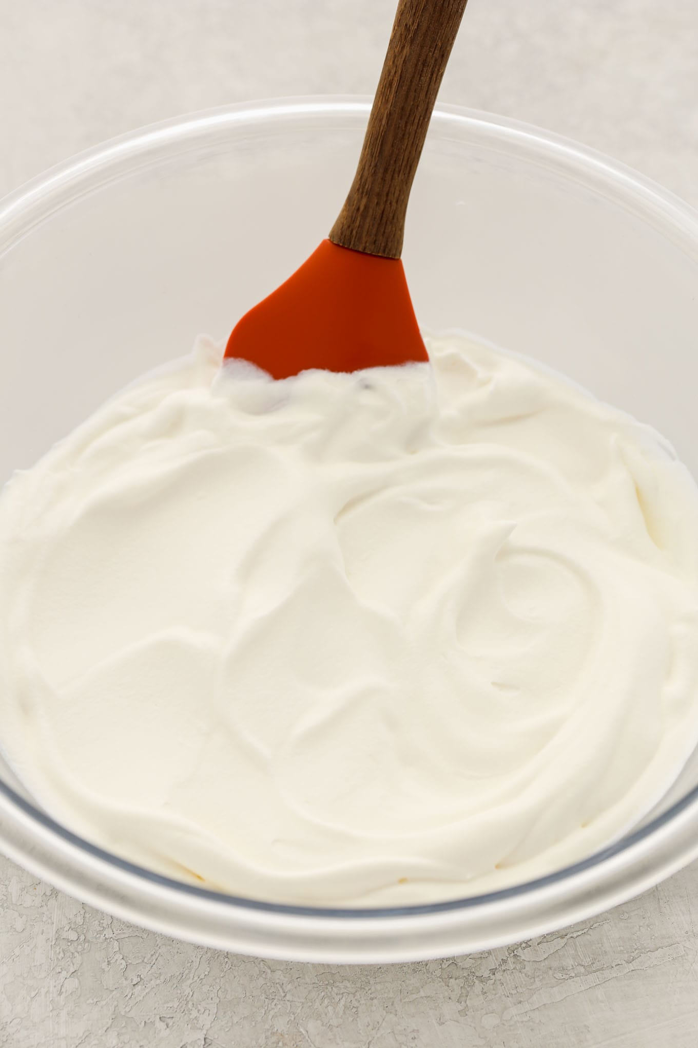 A glass bowl filled with homemade whipped cream and a rubber spatula in it.