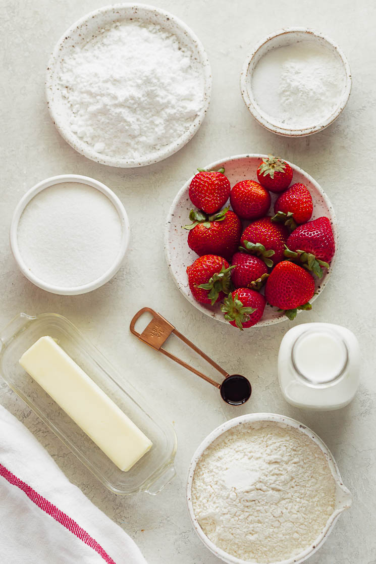 Several of the ingredients needed for strawberry shortcake on a gray surface.