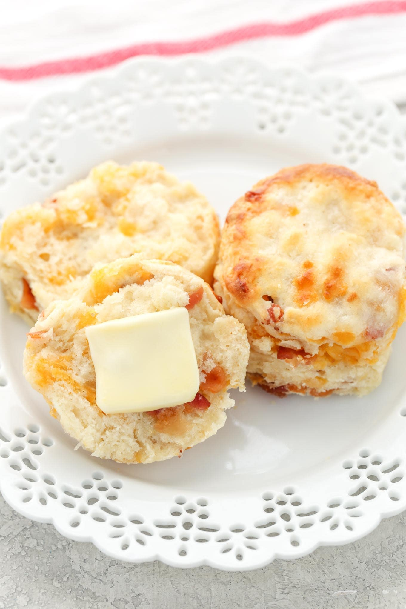 Two bacon cheddar biscuits on a white plate. One biscuit is cut in half and has a pat of butter on it.