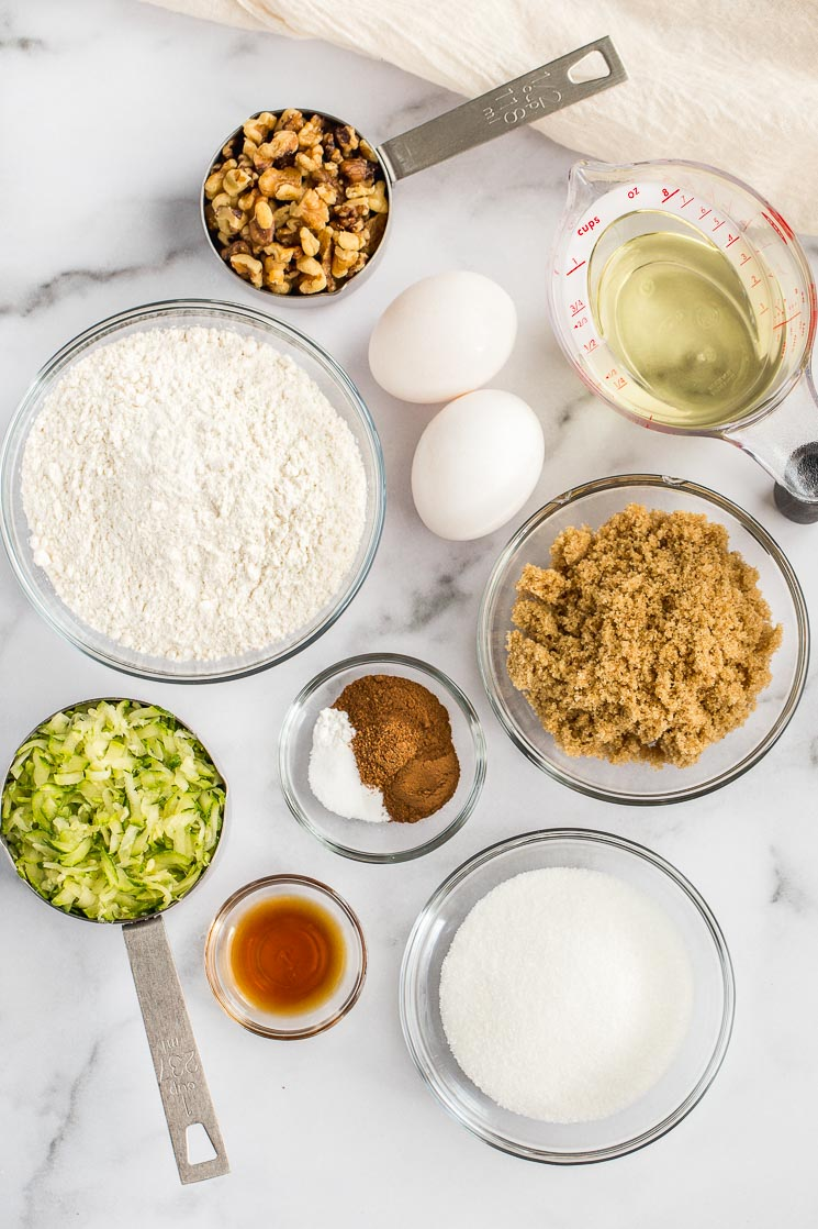 The ingredients needed for zucchini bread sitting on top of a marble surface.