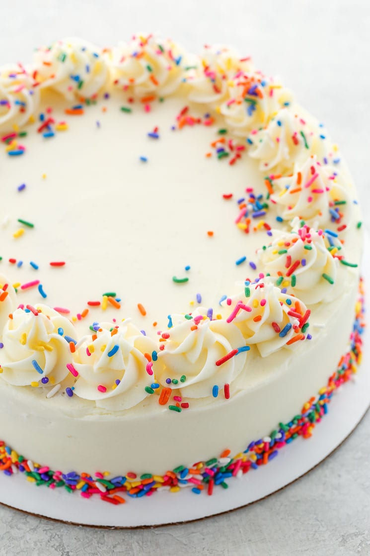 A fully decorated white cake with sprinkles sitting on top of a gray surface.