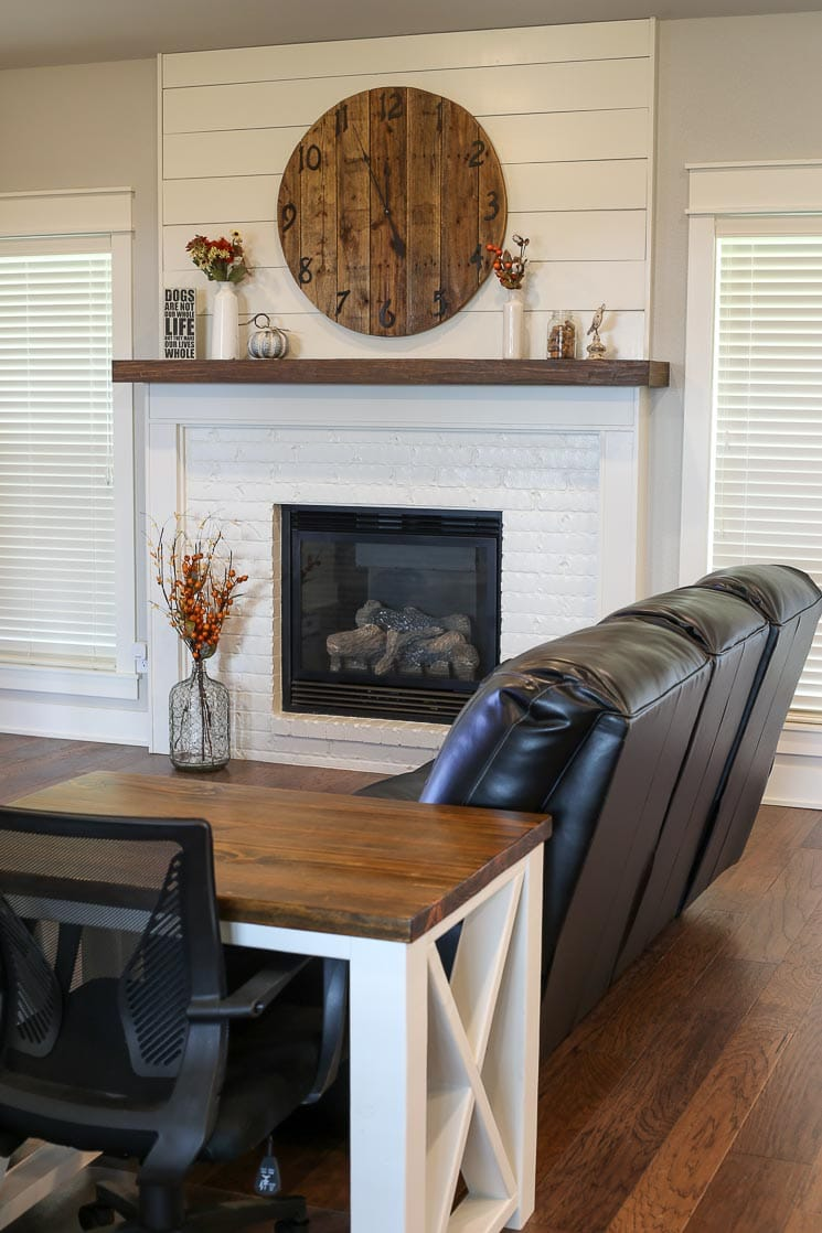 A picture of a living room with a white fireplace and farmhouse table.