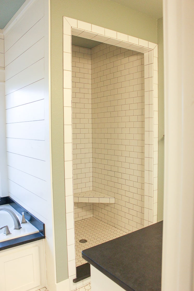 A bathroom with white subway tiles and a whirlpool tub with shiplap.