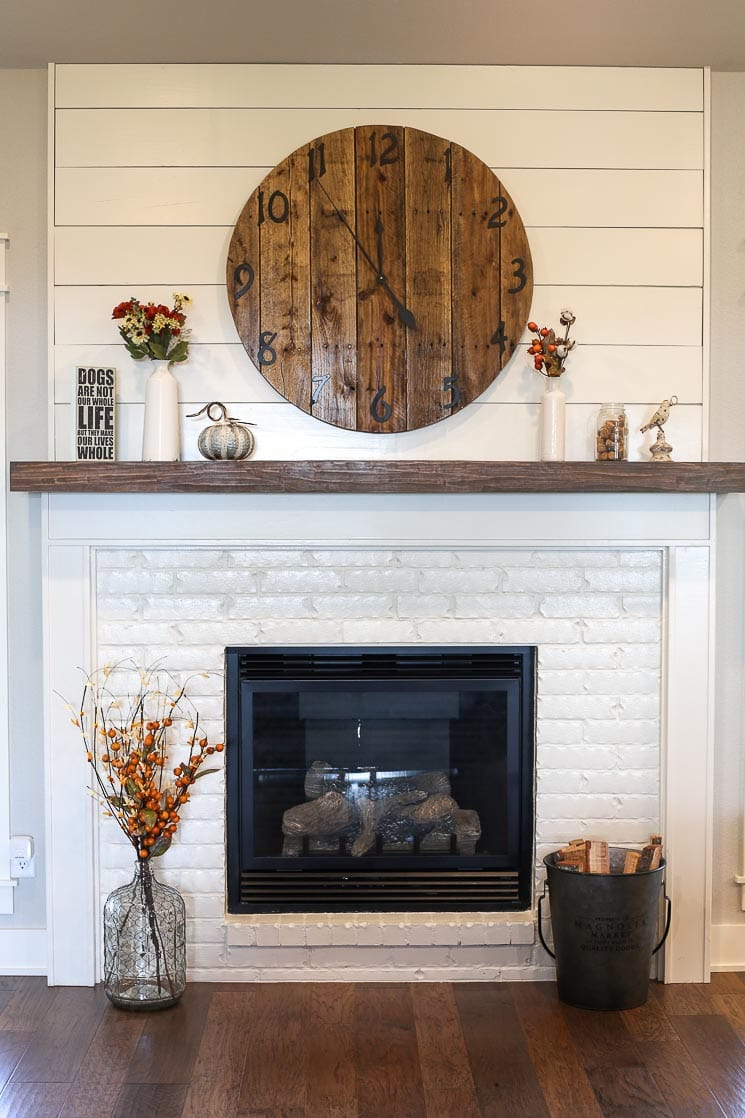 A picture of a fireplace with painted white brick and shiplap.