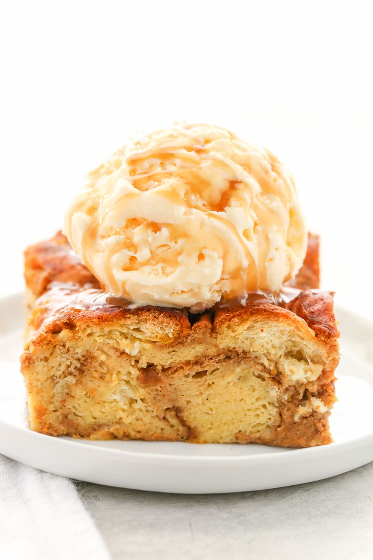 Slice of pumpkin bread pudding topped with ice cream on a white plate.