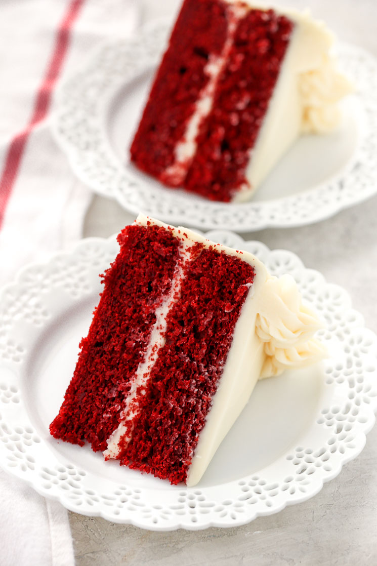 Two slices of red velvet cake topped with cream cheese frosting on decorative white plates and a white napkin on the side.